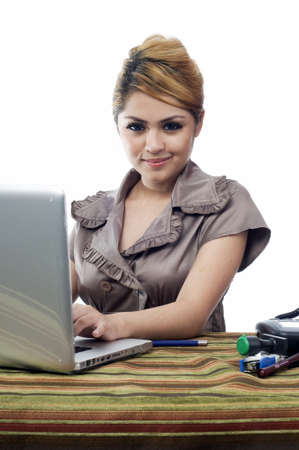 Young energetic asian business woman smile while typing isolated white backgrouind photo