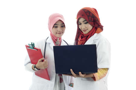 Two young muslim lady doctor view notebook isolated white background