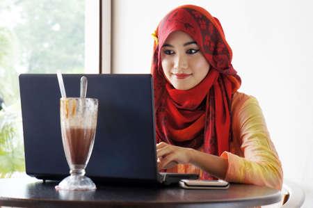 Jonge moslim stijlvolle vrouwen bezig te typen op de notebook op cafe