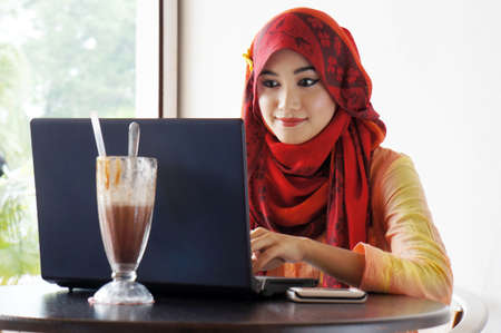 Young muslim stylish women busy typing on notebook at cafe Stock Photo