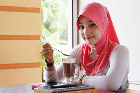 Young muslim stylish women holding a spoon over a drinks looking at camera while books and drinks on the table photo
