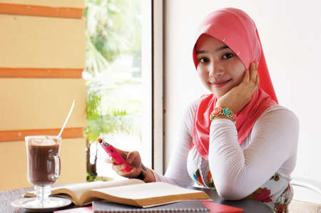 Young muslim stylish women smile while writing text messaging at the cafe