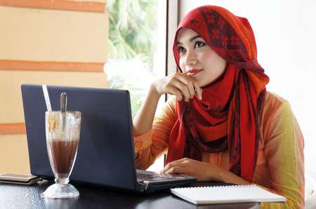 Jonge moslim stijlvolle vrouwen denken over iets wat in een cafe Stockfoto