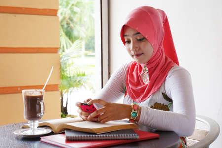 Jonge moslim stijlvolle vrouwen het schrijven van sms-berichten in een cafe met boeken en drankjes op de tafel