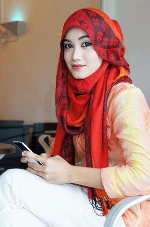 femme musulmane: Les jeunes musulmans les femmes élégantes messagerie texte écrit dans un café à la recherche à la caméra