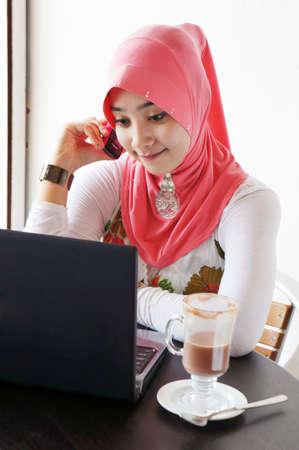 mujeres musulmanas: Las mujeres j�venes con estilo musulmanes que hablan por tel�fono m�vil delante de la computadora port�til en un caf�