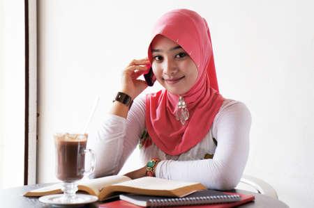 mujeres musulmanas: Las mujeres j�venes con estilo musulm�n hablando por tel�fono m�vil en el caf� con los libros y las bebidas en la mesa
