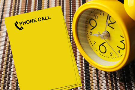 reminders: Yellow phone call notes beside close up retro alarm clock on color mat shows 8 oclock