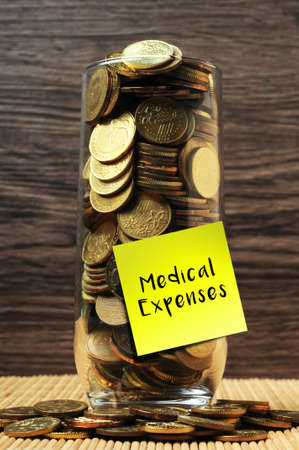 medical expenses: Overload coins in glass with sticky notes medical expenses