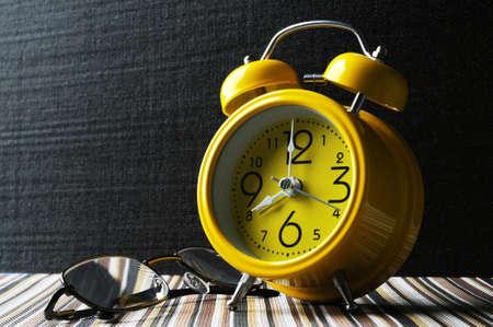 amarillo y negro: Amarillo retro reloj de alarma en la estera de color muestra 8 en punto aislado de fondo negro