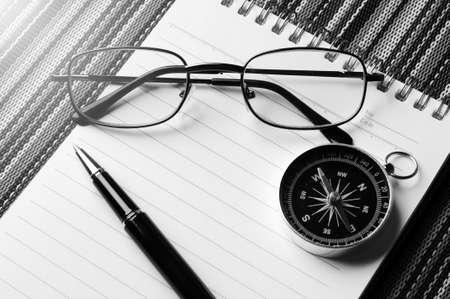 Zwarte en witte pektakels, kompas en pen op de notitieblok op de mat