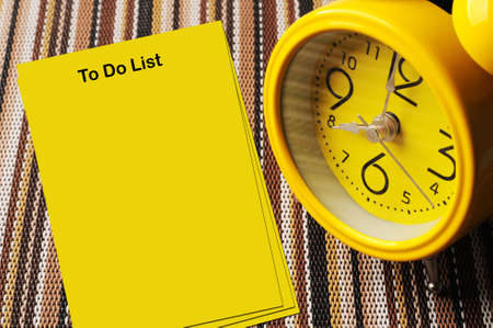 come up to: Yellow to do list notes beside close up retro alarm clock on color mat shows 8 oclock Stock Photo