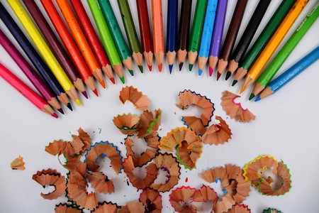 Colored pencils in row and shavings on white background Stockfoto
