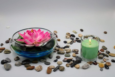 Bowl with blue water rose lily and lit candle Stock Photo
