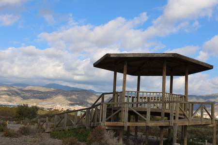 Wooden gazebo with mountain background and cloud covered sky
