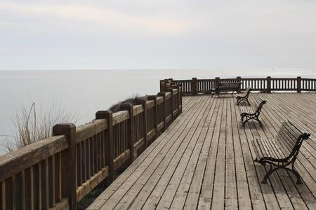 Wooden esplanade on the sea shore with benches to relax in Retamar Almería Stock Photo