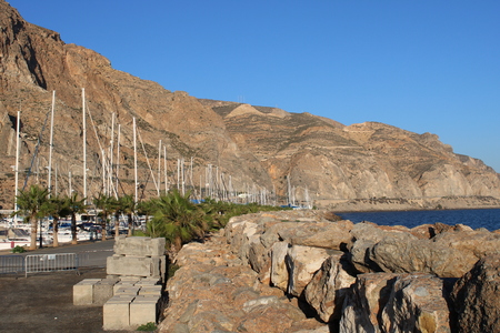 Stone pier in the marina at the foot of the mountain