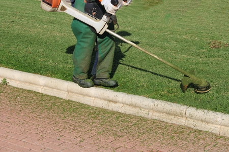 Worker with green overalls mowing the lawns of public gardens