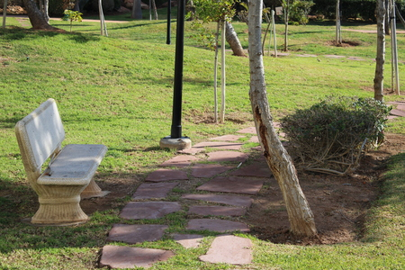 White stone bench in recreational park and stone path