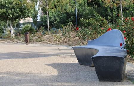 Modern cement bench in recreational park of Almería and diverse vegetation 版權商用圖片