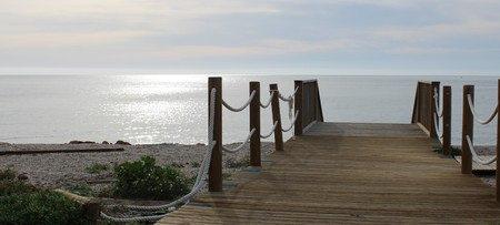 Wooden bridge for walks on the beach of Almerimar , Almeria