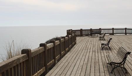 Wooden esplanade on the sea shore with benches to relax in Retamar of Almería