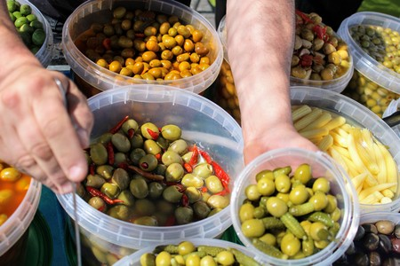 Buckets full of green and black olives , pickles and baby corn all pickled to mediterranean style 写真素材 - 123663503