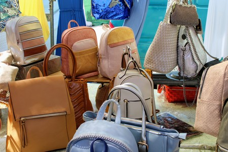 Shelf with leather bags and backpacks in different shades 写真素材 - 123663894
