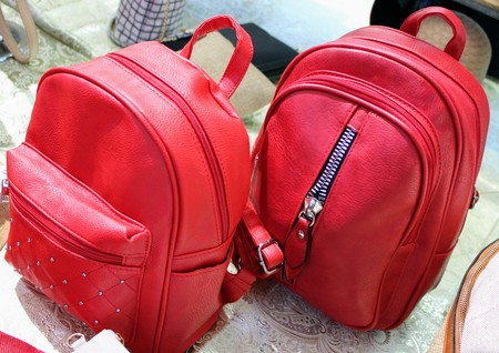 Beautiful red leather backpacks with zippers and different models 写真素材 - 123664002