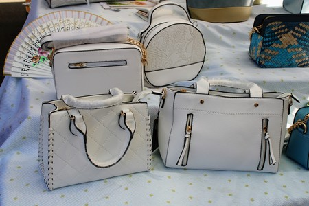White leather bags of different designs and fan with beautiful drawing