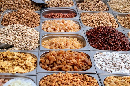 Variety of nuts in containers exposed in the market Stock Photo - 123664220