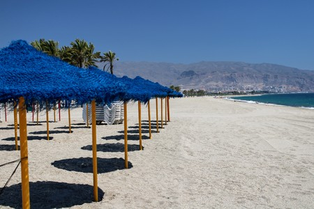 Sun umbrellas and sunbeds in the sand on the shore of the mediterranean sea
