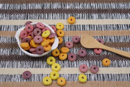 Small white bowl with colorful round cereals and wooden spoon 写真素材