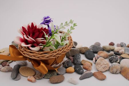Small plastic basket with brown bow and red flowers on stones
