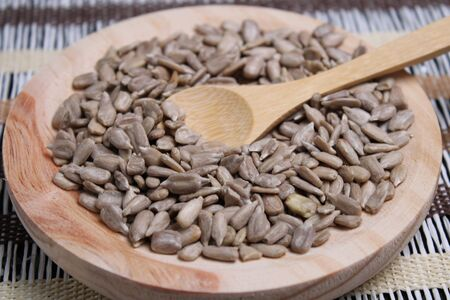 Round wooden board with peeled sunflower seeds and wooden spoon
