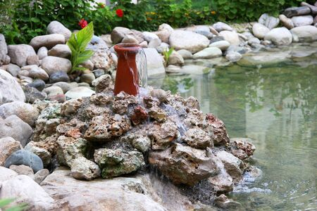 beauty fountain: a fountain of clear water on the stones in the lake