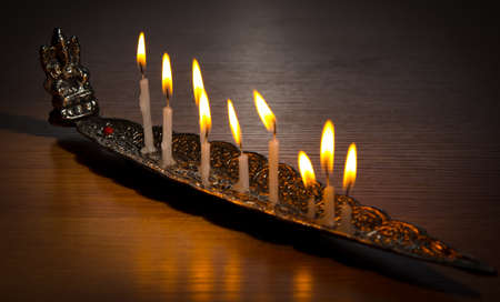 candelabrum: nine Church candles in a silver candelabrum with the figure of the Buddha on a dark background