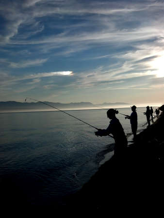 Silhouettes of people fishing for salmon along the shore with a sundog  photo