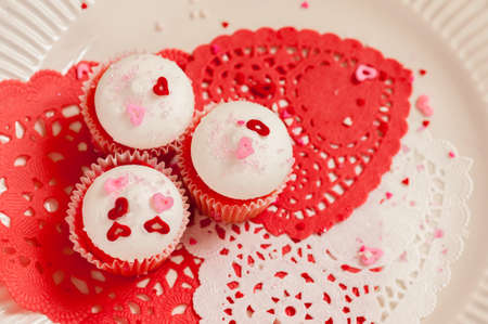 doilies: Three Valentines Day cupcakes with white frosting and red and pink sprinkles on colorful paper doilies and a white plate. Stock Photo