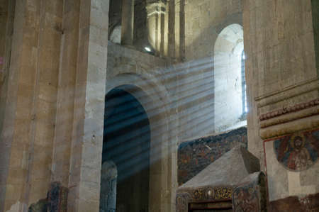 penetrate: This is indoor scene of ancient church from Ananuri castle comlex. Shoots of sunlight penetrate intrerior space of church.
