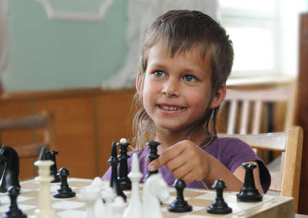 Little girl is playing chess. She is smiling.