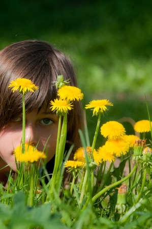 ablooming: La ragazza guarda attraverso i denti di leone. E 'primavera. Archivio Fotografico