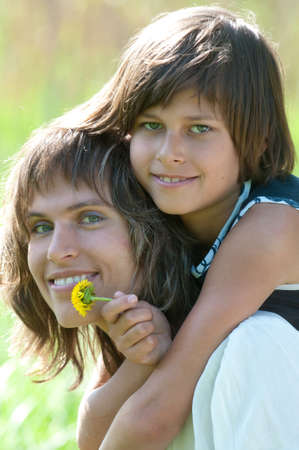 Mother and daughter posing happily on nature background. The girl has hold of yellow flower in her hand. photo