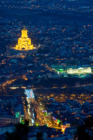 The photo of illuminated Cathedral and presidential palace is taken against the night cityscape background. The Holy Trinity Cathedral of Tbilisi is the main Cathedral of the Georgian Orthodox Church located in Tbilisi, the capital of Georgia. photo