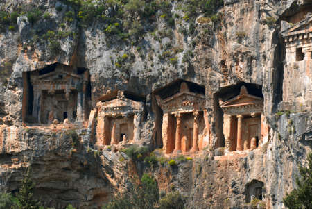 There are four necropoli of Lycian rock-cut tombs in the form of temple fronts carved into the vertical faces of cliffs in the Dalyan river valley, Turkey. Columns and bas-reliefs of ancient tombs is seen well. photo