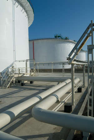 Petroleum storage reservoires and pipelines are white. Industry object is captured against a blue sky background. photo
