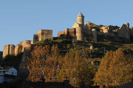 Narikala is an ancient fortress in Tbilisi. The stronghold and  St Nicholas church are standing on the top  of mountain  against the blue sky background.