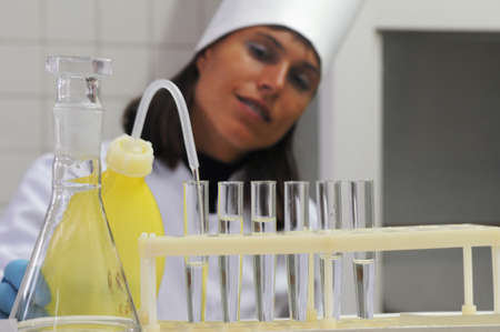 The woman fills glass tubes with liquid.She is dressed in white doctors overall. photo