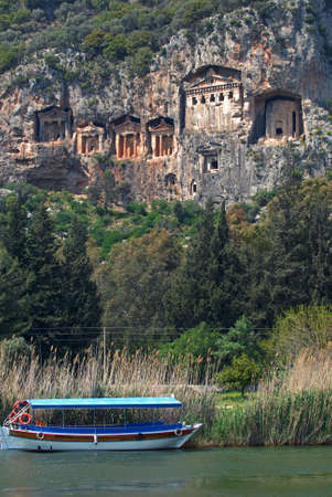 Necropolis of Lycian rock-cut tombs in the form of temple fronts carved into the vertical faces of cliffs in the Dalyan river valley, Turkey  Tourist boat moored near waterside  photo