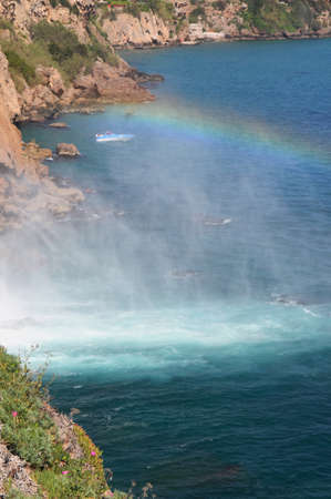 Limpid waters of the Duden Falls  Antalya,Turkey   drop off a rocky cliff directly into the Mediterranean Sea in a dazzling show  A rainbow is against the blue sea  photo